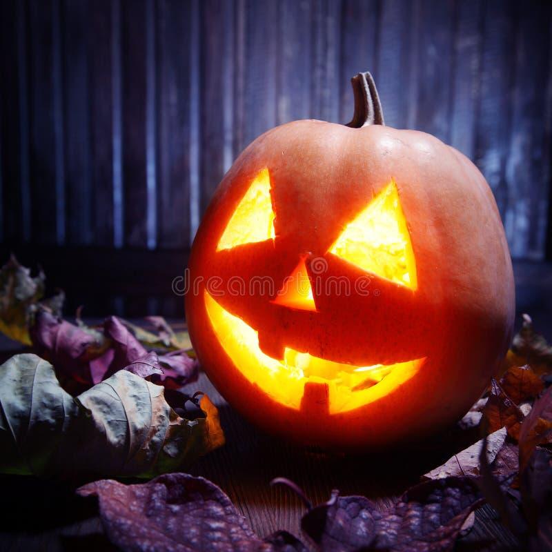 Levante la cara de la calabaza de Halloween de las linternas de o en fondo de madera imagen de archivo libre de regalías