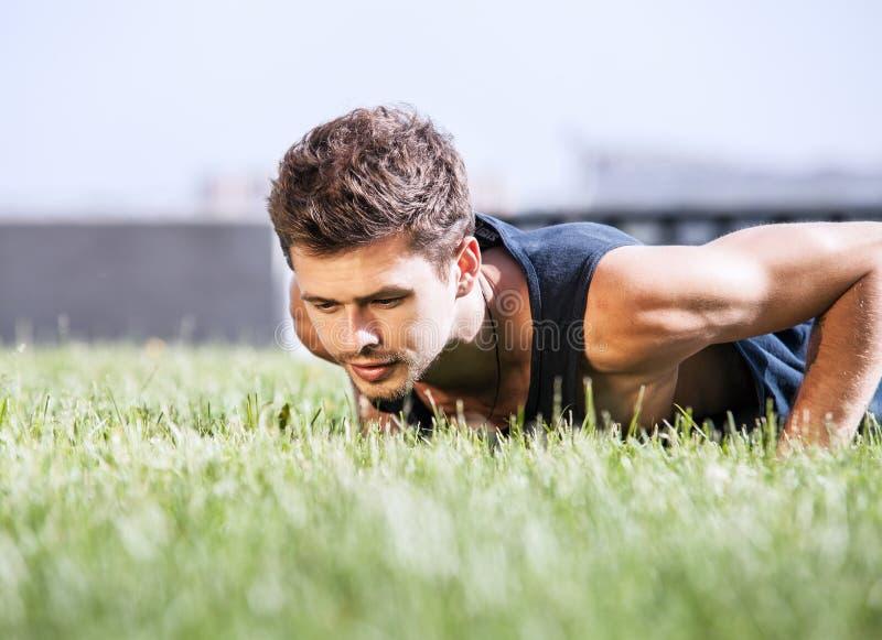 Levante o homem muscular no gramado verde no parque da cidade imagem de stock