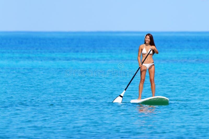 Levante-se a mulher da placa de pá que paddleboarding fotos de stock royalty free