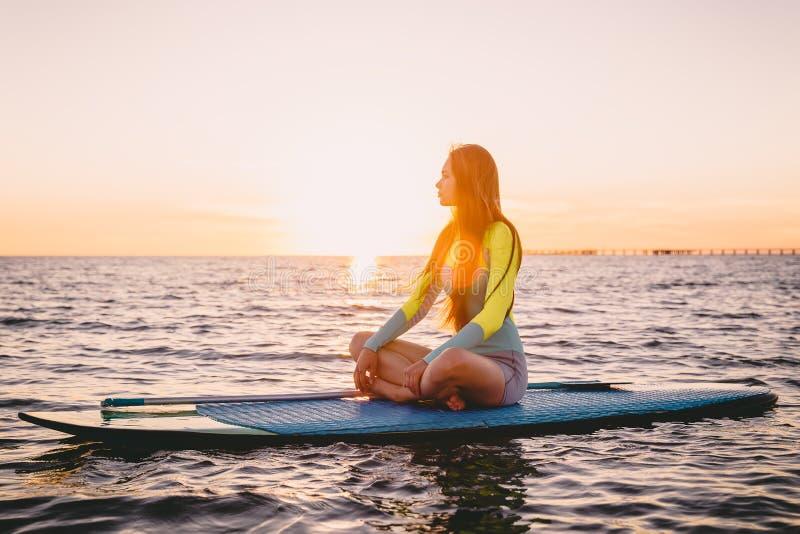 Levante-se o embarque da pá em um mar quieto com cores mornas do por do sol A menina magro nova está relaxando no oceano imagens de stock