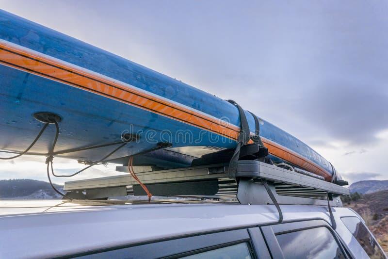 Levante-se o paddleboard em grades de tejadilho do suv imagens de stock
