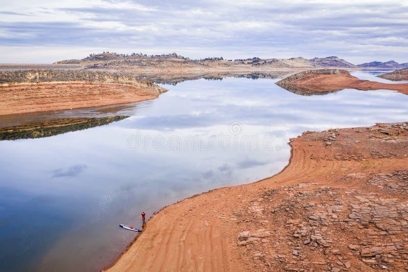 Levante-se o paddler em um lago da montanha imagens de stock royalty free