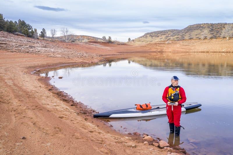 Levante-se o paddler em uma costa do lago foto de stock