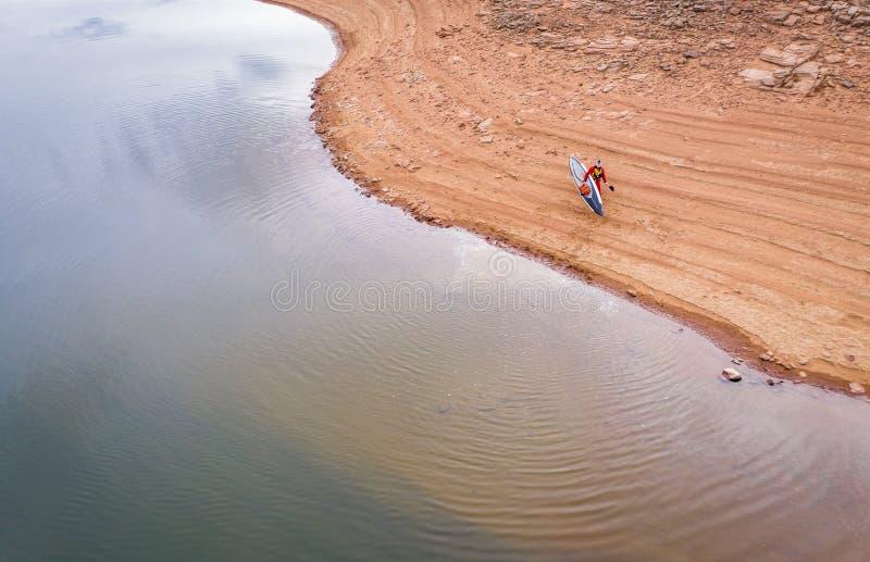 Levante-se o paddler em uma costa do lago imagem de stock royalty free