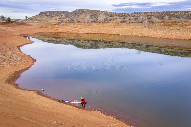 Levante-se o paddler em uma costa do lago imagens de stock royalty free