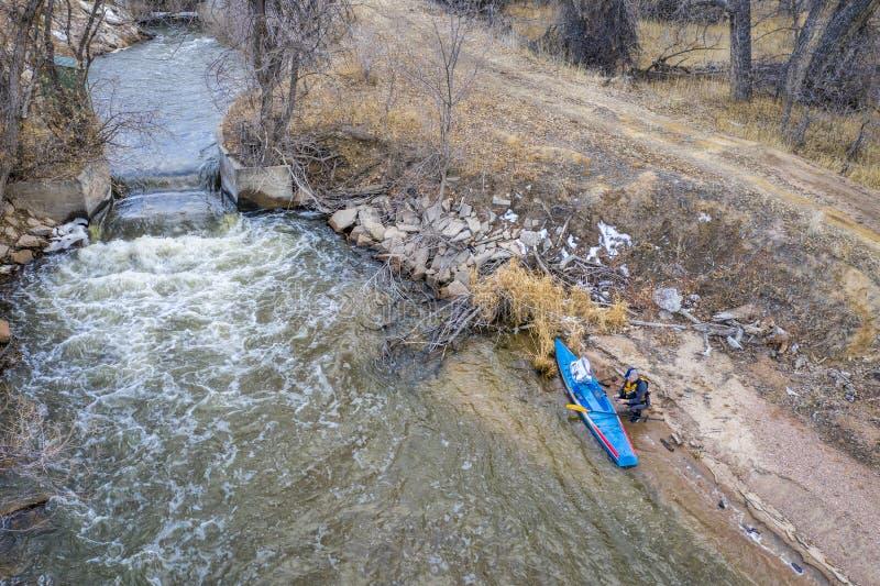Levante-se o paddler em uma costa do rio foto de stock royalty free