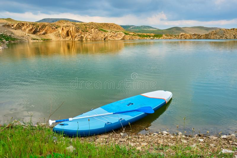 Levante-se o SUP da placa de pá na borda de um smarald/lago verde, isolado, isolado, com luz morna do por do sol - lago Iacobdeal foto de stock