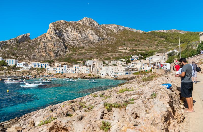 Visitors enjoy the coastline during their trip of small village on Levanzo island, the smallest of the Egadi. royalty free stock photo