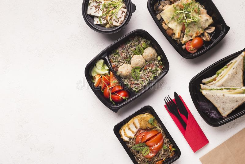 Leve embora o alimento saudável em umas caixas negras para a nutrição da dieta no branco foto de stock
