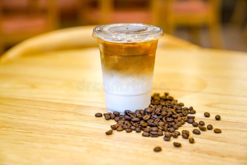 Leve embora o Latte com feijão de café ao redor na tabela de madeira foto de stock