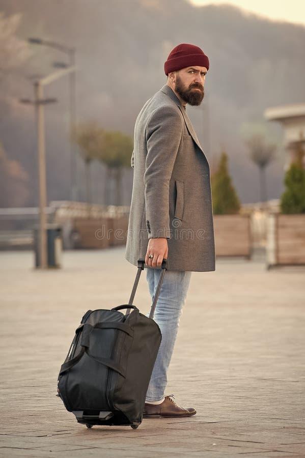Leve o saco do curso Curso farpado do moderno do homem com o saco da bagagem nas rodas Adjust que vive na cidade nova Viajante co foto de stock