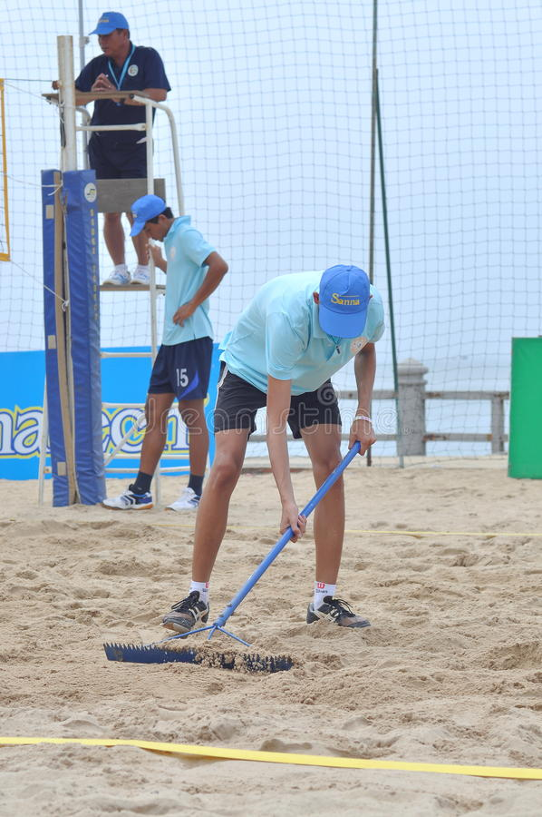 Leveling the beach after a volleyball match in Nha Trang city royalty free stock image