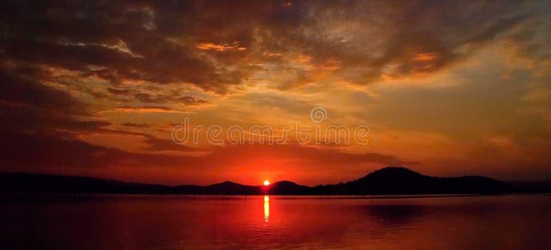 Levendige bewolkte karmozijnrode zonsopgang met waterbezinningen royalty-vrije stock afbeelding