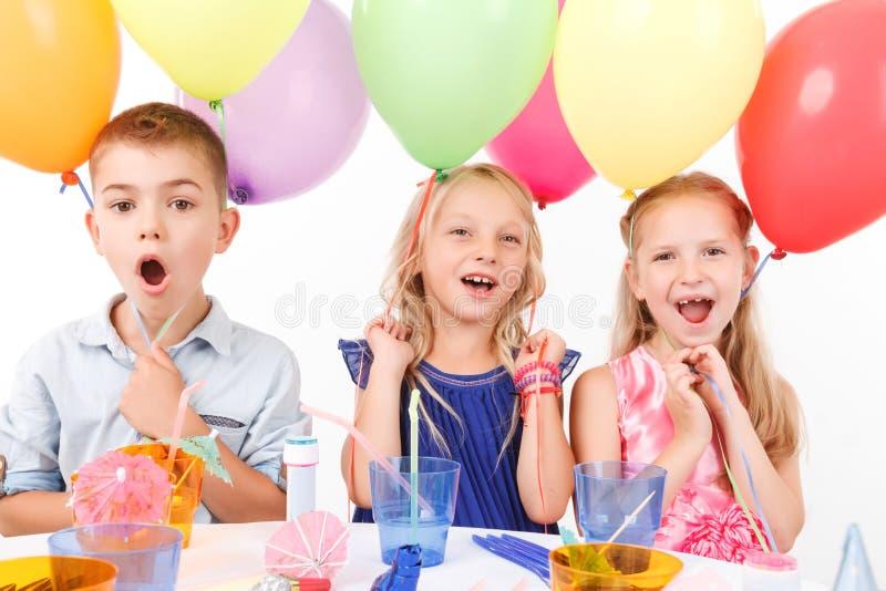 Levendige kinderen die bij de lijst zitten royalty-vrije stock afbeeldingen