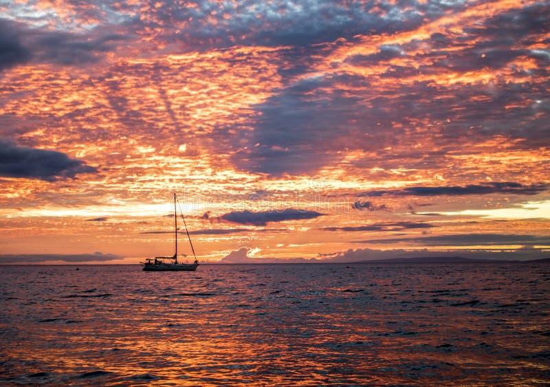 Levendige Oranje Zonsondergang die in Oceaanoppervlakte met Zeilboot nadenken royalty-vrije stock afbeeldingen