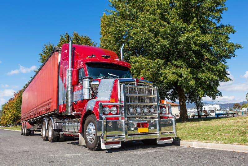 Levendige rode semi die vrachtwagen in landelijke stad, Australië wordt geparkeerd royalty-vrije stock afbeeldingen