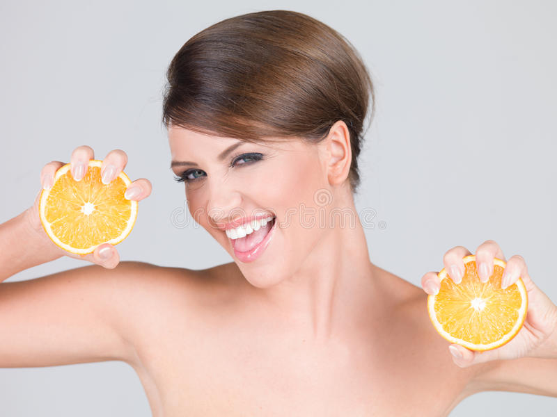 Levendige speelse vrouw met verse oranje plakken stock afbeelding
