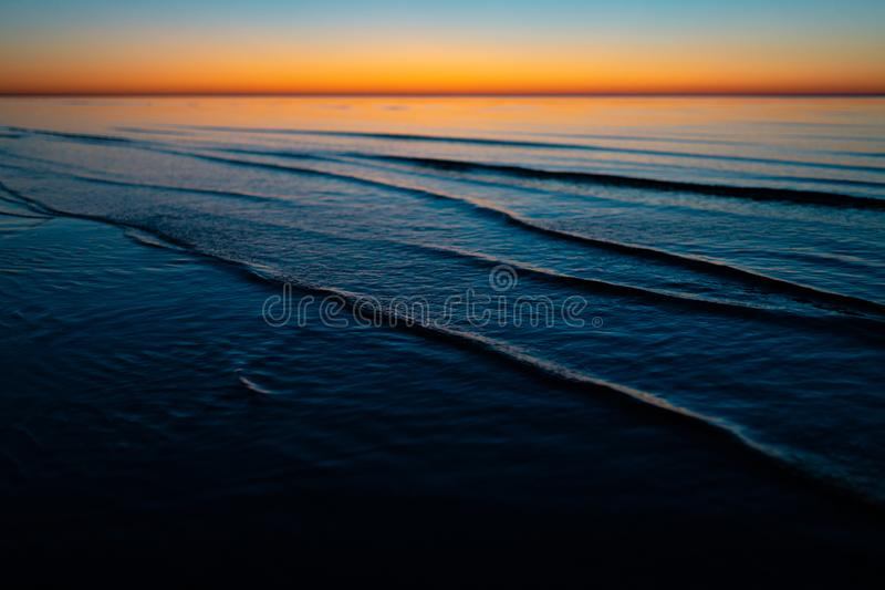 Levendige verbazende zonsondergang in Baltische Staten - de Schemer in het overzees met horizon verlicht door de zon stock afbeelding