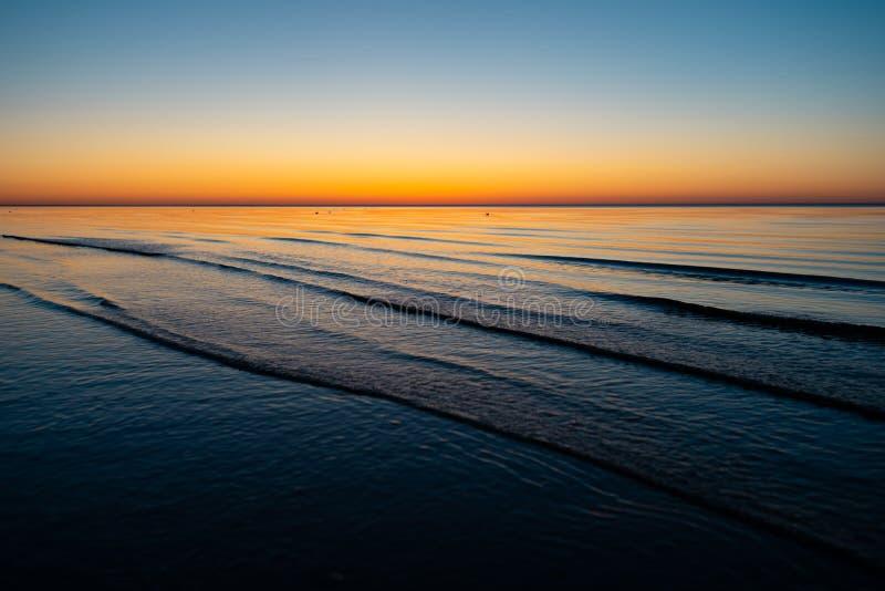 Levendige verbazende zonsondergang in Baltische Staten - de Schemer in het overzees met horizon verlicht door de zon stock foto