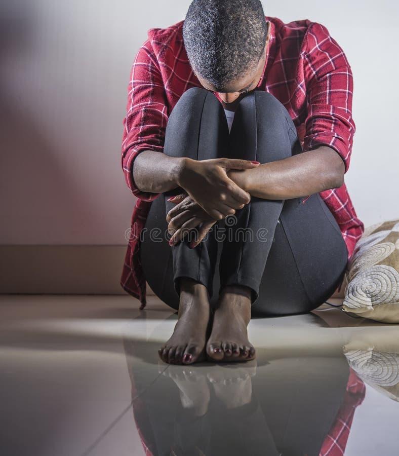 Levensstijl binnen portret van het jonge droevige en gedeprimeerde zwarte Afrikaanse Amerikaanse de vloer van de vrouwenzitting t stock foto