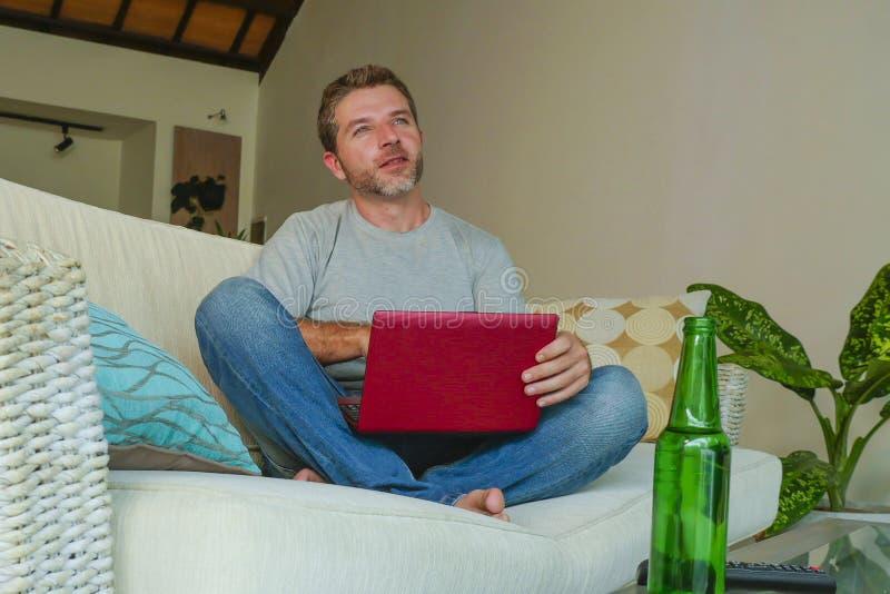 Levensstijl binnen portret van jonge aantrekkelijke en knappe gelukkige de banklaag die van de mensenzitting thuis online met lap stock afbeeldingen