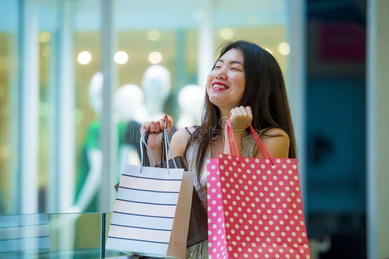 Levensstijl binnen portret van jonge gelukkige en mooie Aziatische Koreaanse vrouw dragende het winkelen zakken in wandelgalerij  stock fotografie