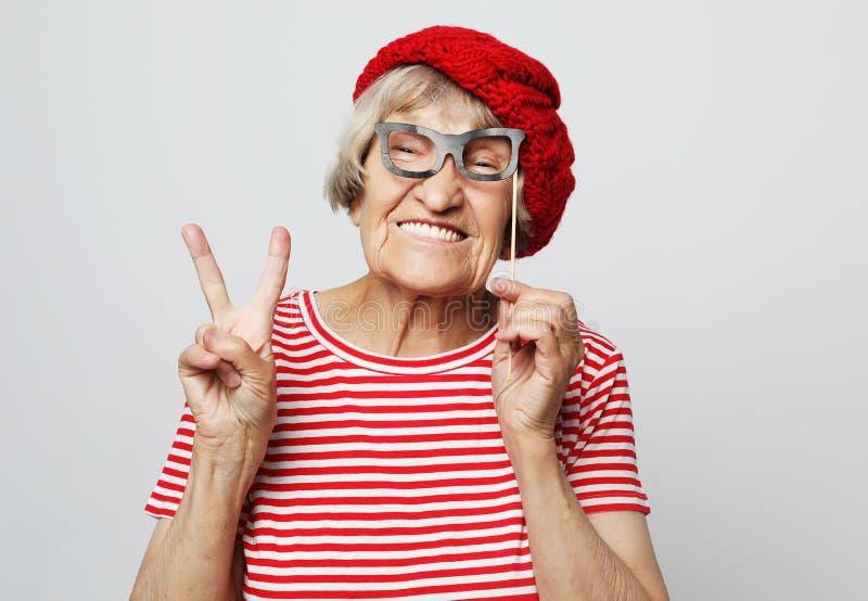 Levensstijl, emotie en mensenconcept: grappige grootmoeder met valse glazen, lach en klaar voor partij stock fotografie