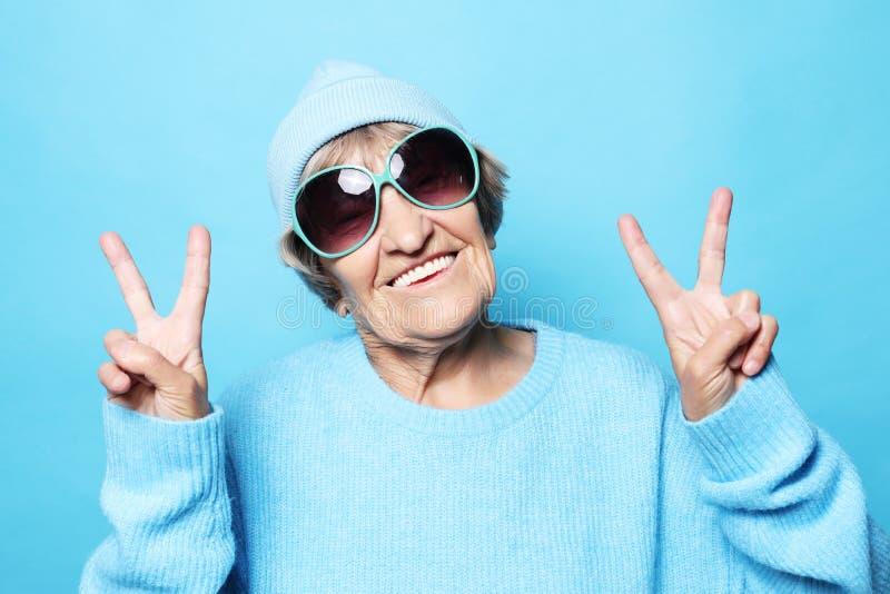 Levensstijl, emotie en mensenconcept: Grappige oude dame die blauwe sweater, hoed en zonnebril dragen die overwinningsteken tonen royalty-vrije stock afbeelding