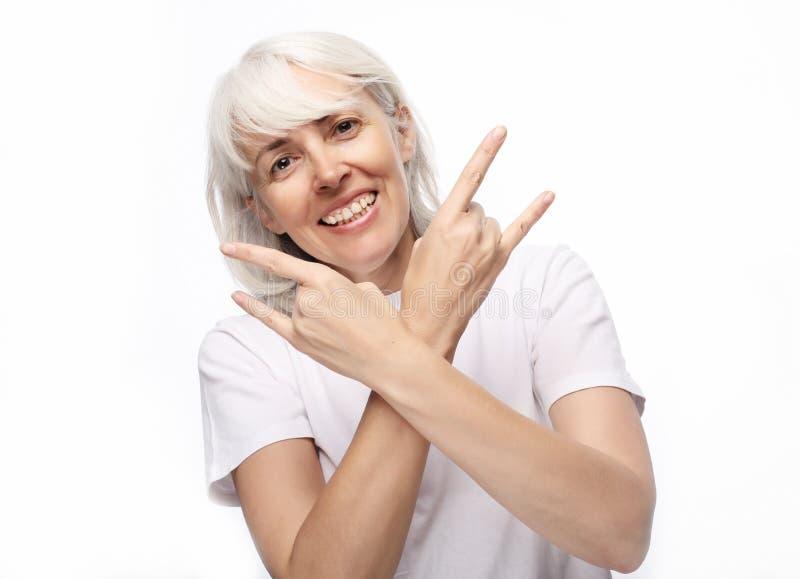 Levensstijl, emotie en mensenconcept: Hogere vrouw die toevallige die het doen funky actie dragen op witte achtergrond wordt geïs stock fotografie