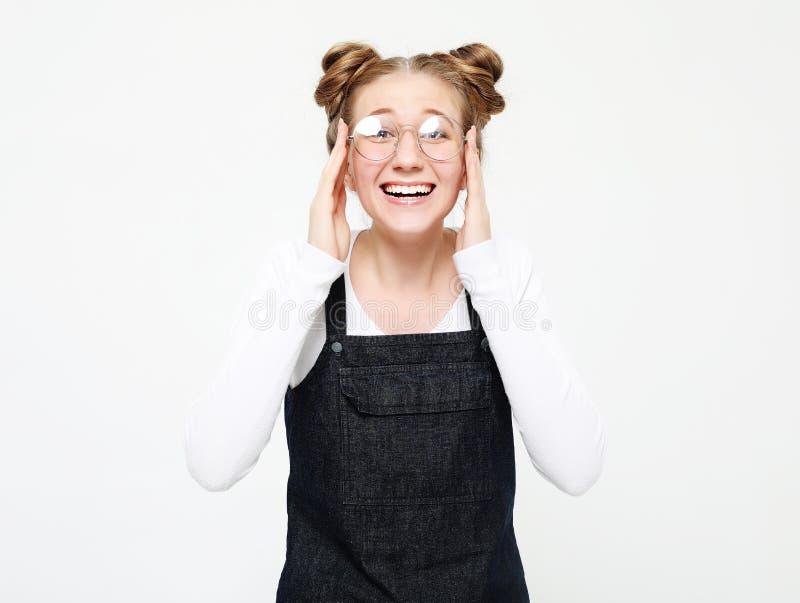 Levensstijl, emotie en mensenconcept: verraste mooie jonge vrouw over lichtgrijze achtergrond stock afbeelding