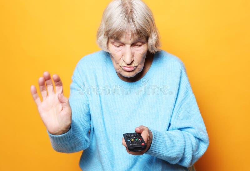 Levensstijl en mensenconcept: de grappige oma houdt een TV over gele achtergrond ver royalty-vrije stock foto