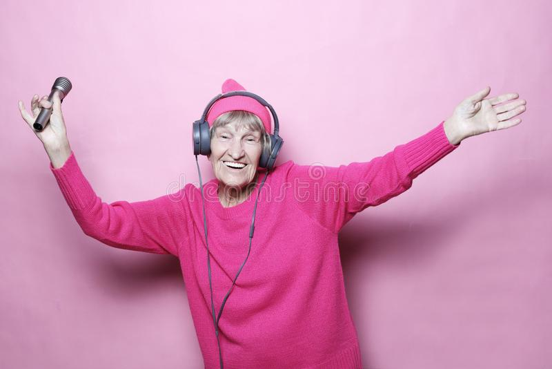 Levensstijl en mensenconcept: Grappige oude dame het luisteren muziek met hoofdtelefoons en het zingen met mic over roze achtergr stock foto