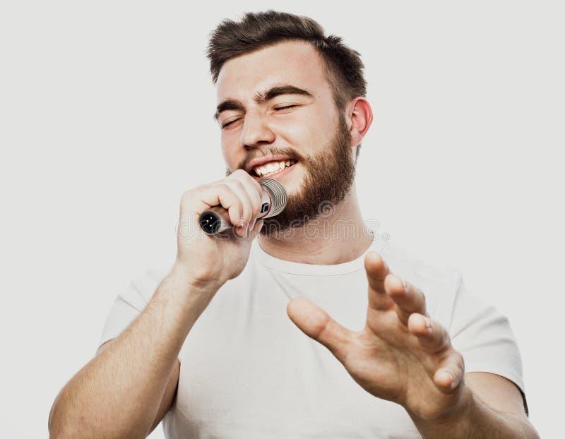 Levensstijl en mensenconcept: jonge mens het zingen met microfoon stock foto