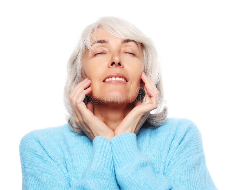 Levensstijl en mensenconcept: Sluit omhoog portret van het gelukkige hogere vrouw dromen met gesloten ogen over witte achtergrond royalty-vrije stock foto