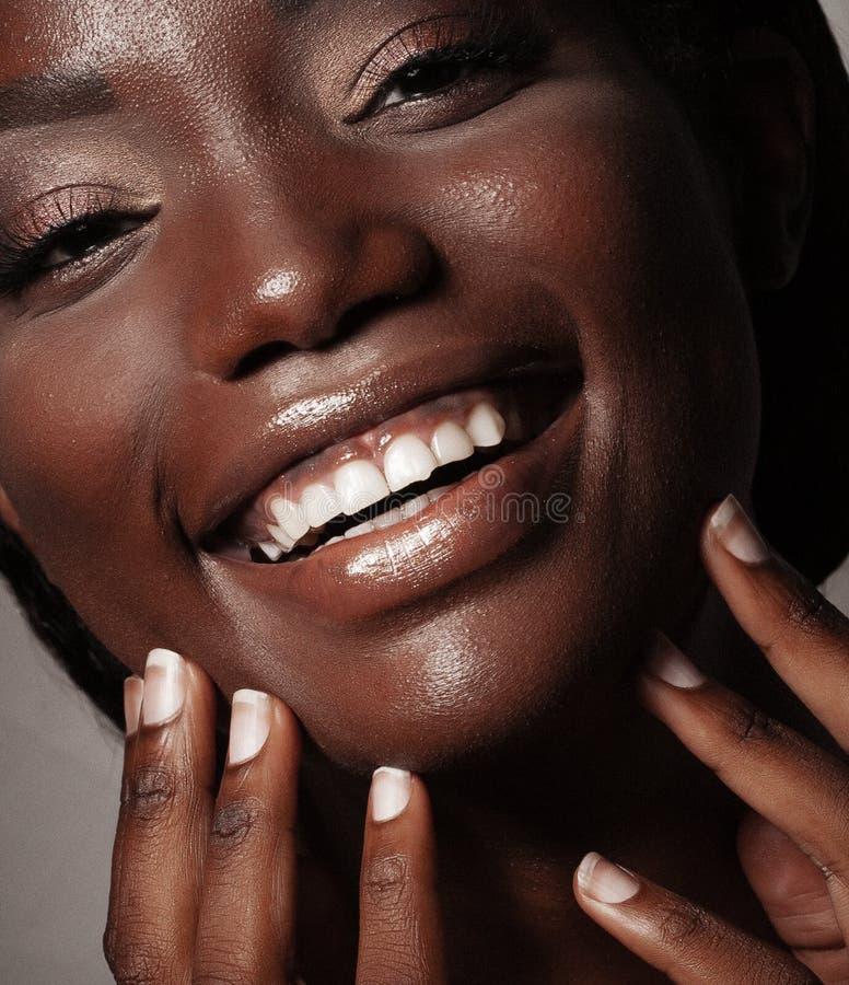Levensstijl en mensenconcept: Sluit omhoog portret van het zekere Afrikaanse Amerikaanse vrouw lachen stock foto