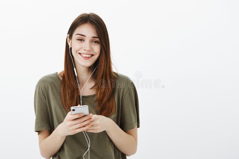 Levensstijl en mooi mensenconcept Positief onbezorgd stedelijk wijfje met bruin binnen haar, het luisteren goede muziek royalty-vrije stock fotografie