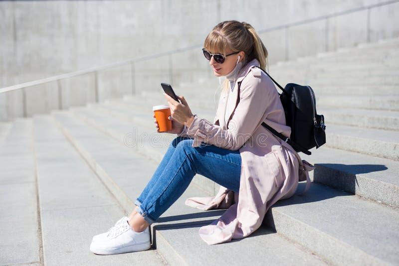 Levensstijl en reisconcept - openluchtportret van jonge vrouwenzitting op treden met smartphone en koffie stock foto's