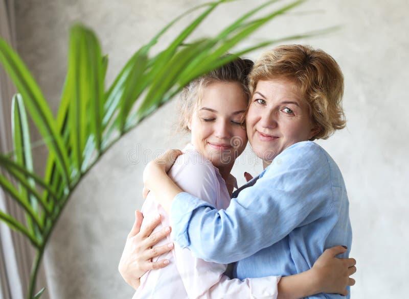 Levensstijl, familie en mensenconcept: Gelukkige jonge vrouw en haar moeder thuis, gelukkige familie royalty-vrije stock fotografie