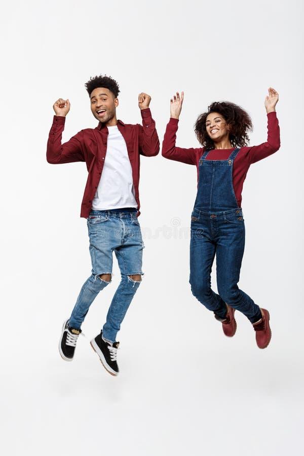 Levensstijl, geluk en mensenconcept: Gelukkig jong mooi Afrikaans Amerikaans paar die over heldere grijze achtergrond springen stock afbeelding