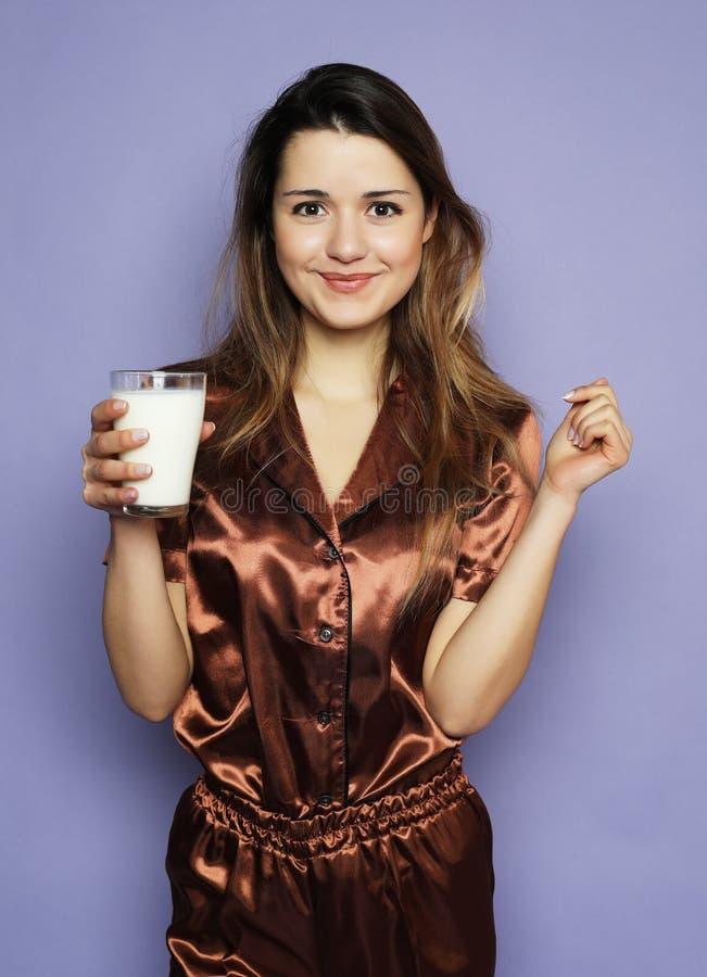 Levensstijl, gezondheid en mensenconcept: het mooie meisje kleedde zich in pyjama'sconsumptiemelk royalty-vrije stock foto's