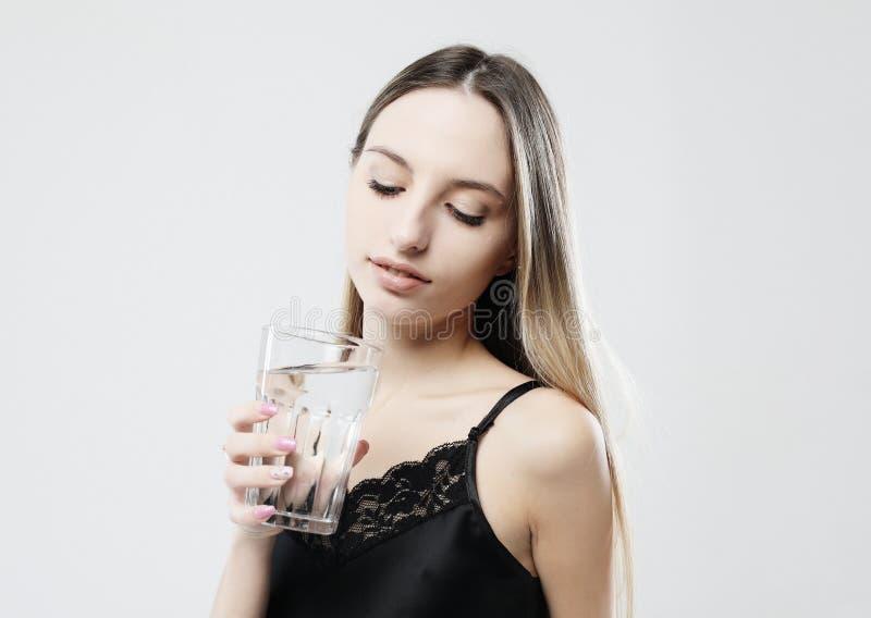 Levensstijl, gezondheid en mensenconcept - jonge vrouw die pyjama's dragen die waterglas houden royalty-vrije stock foto