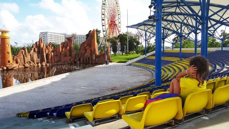 levensstijl, meisje in gele t-shirt, autistische kindzitting op het podium voor het Park met ritten en dekking zijn oren met h royalty-vrije stock afbeelding