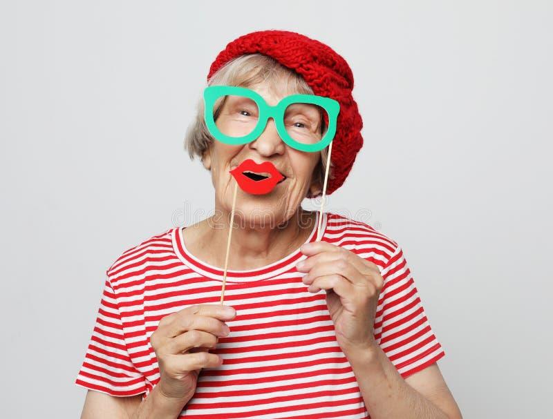 Levensstijl, mensen en partijconcept: grappige grootmoeder die rode kleren klaar voor partij dragen stock afbeelding