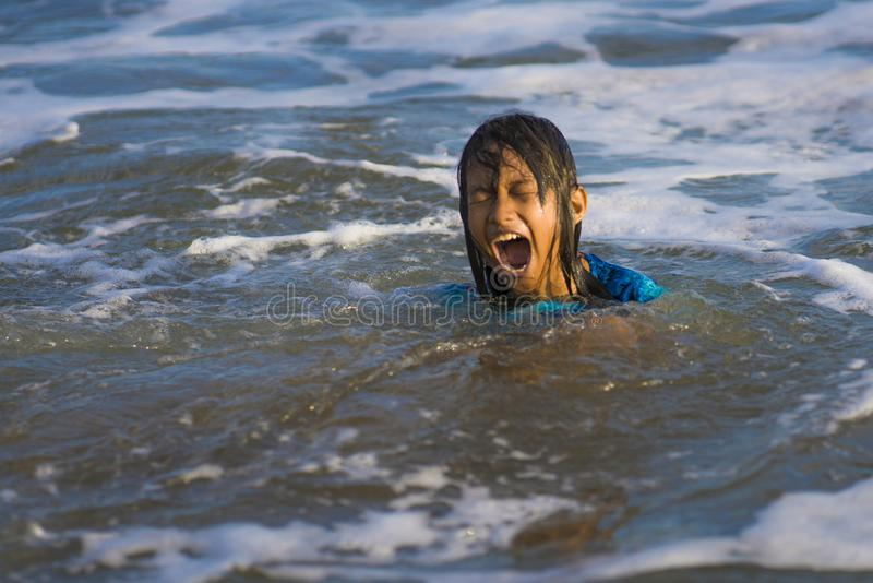 Levensstijl spontaan portret van jong gelukkig en opgewekt kindmeisje die pret hebben bij strand het zwemmen het spelen met het o stock foto