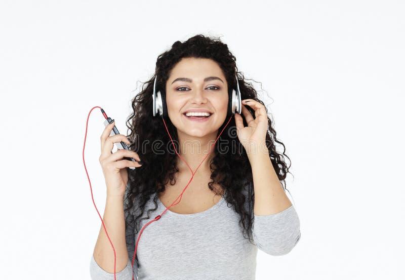 Levensstijl, technologie en mensenconcept: Mooie jonge vrouw die aan muziek in hoofdtelefoons luisteren royalty-vrije stock foto's