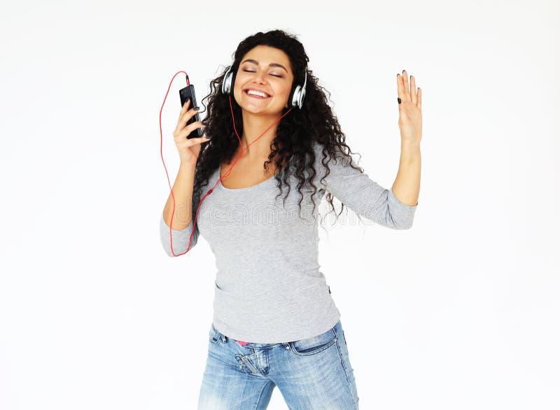 Levensstijl, technologie en mensenconcept: Mooie jonge vrouw die aan muziek in hoofdtelefoons luisteren stock afbeeldingen