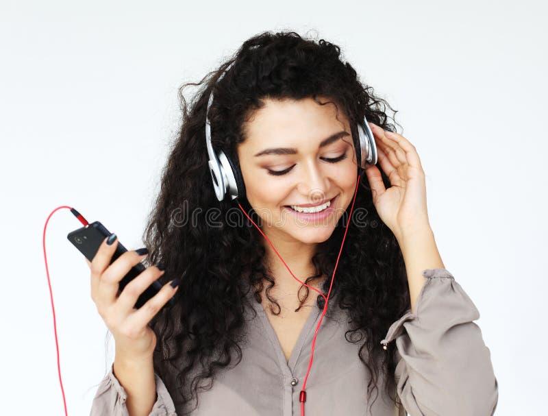 Levensstijl, technologie en mensenconcept: Mooie jonge vrouw die aan muziek in hoofdtelefoons luisteren royalty-vrije stock afbeelding
