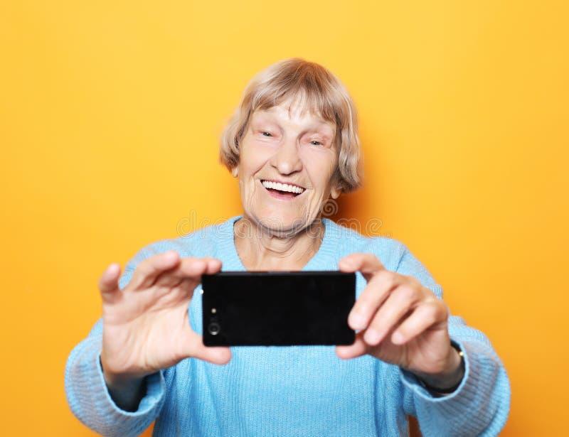 Levensstijl, tehnology en mensenconcept: de oma glimlacht en neemt een selfie over gele achtergrond royalty-vrije stock foto