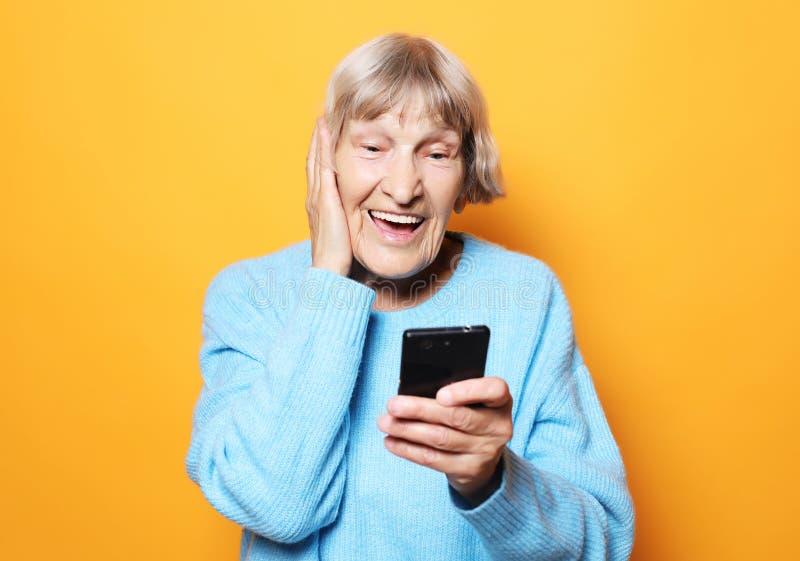 Levensstijl, tehnology en mensenconcept: de oude oma bekijkt haar smartphone en is verrast stock foto