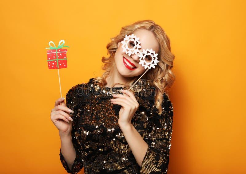 Levensstijl, vakantie en mensenconcept - de vrolijke jonge vrouw in kleding houdt steunen voor een partij en glimlacht stock fotografie